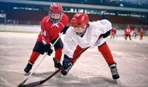 Young hockey players playing against each other.