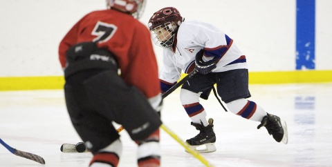 Youth hockey player carrying puck in small area game